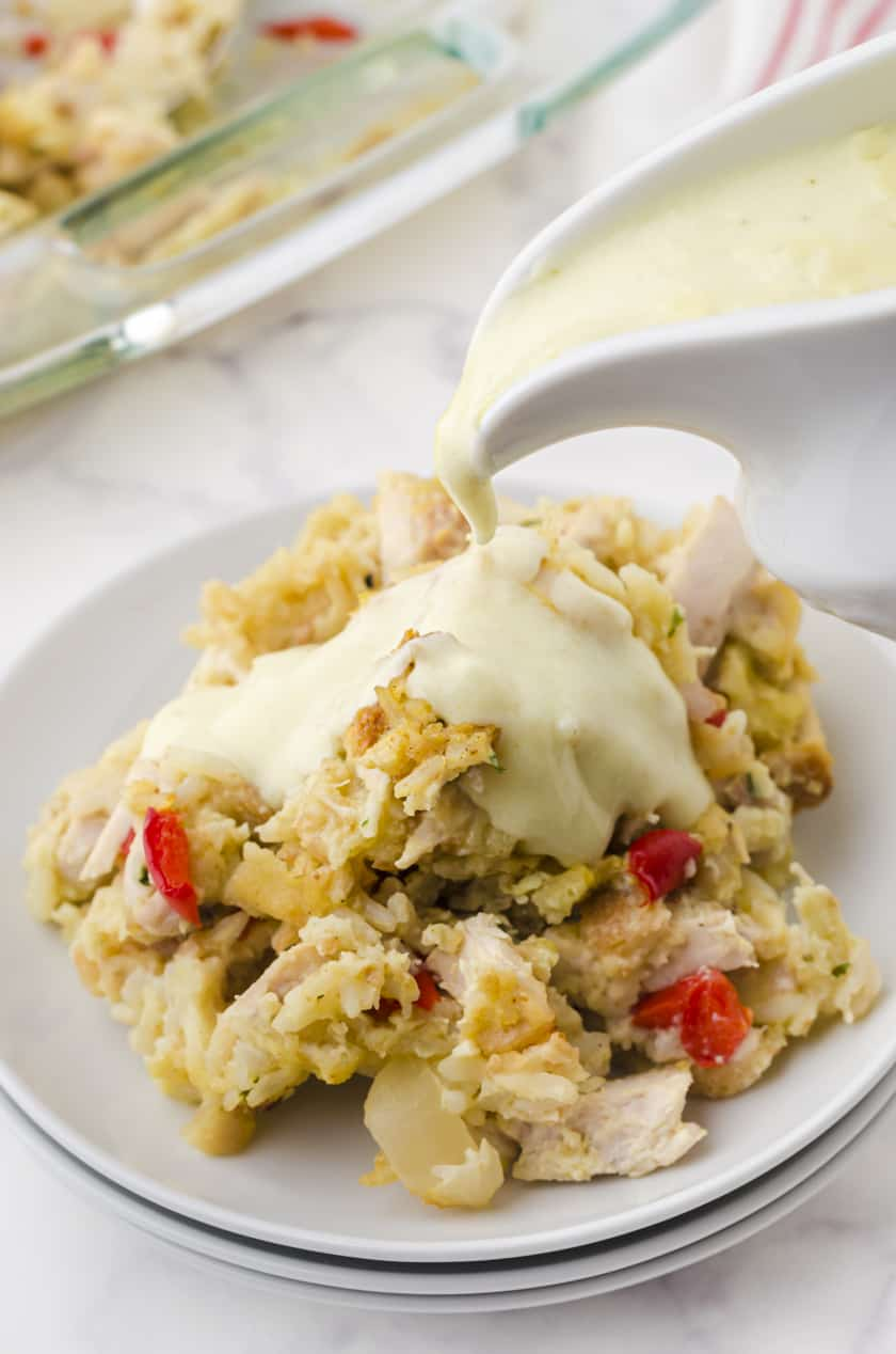 Serving of chicken rice casserole with creamy sauce being poured over it.