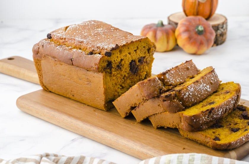 Cake mix pumpkin bread sliced on a wooden cutting board.