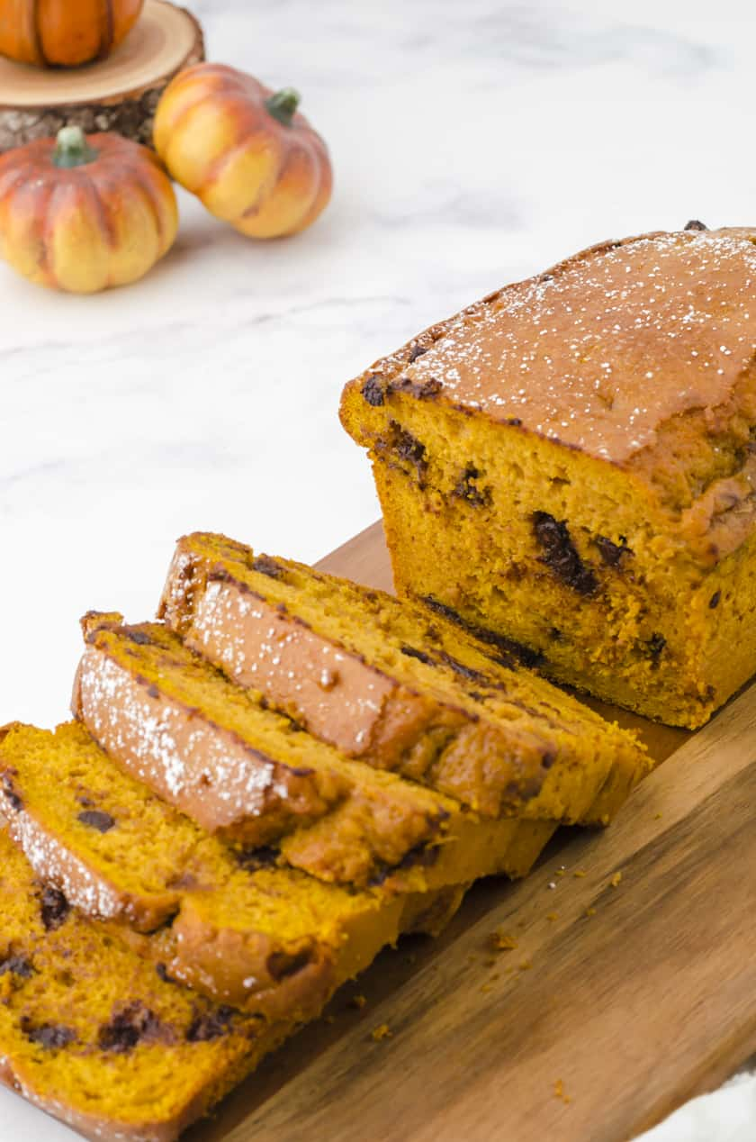 Close up of sliced chocolate chip pumpkin bread on a cutting board.
