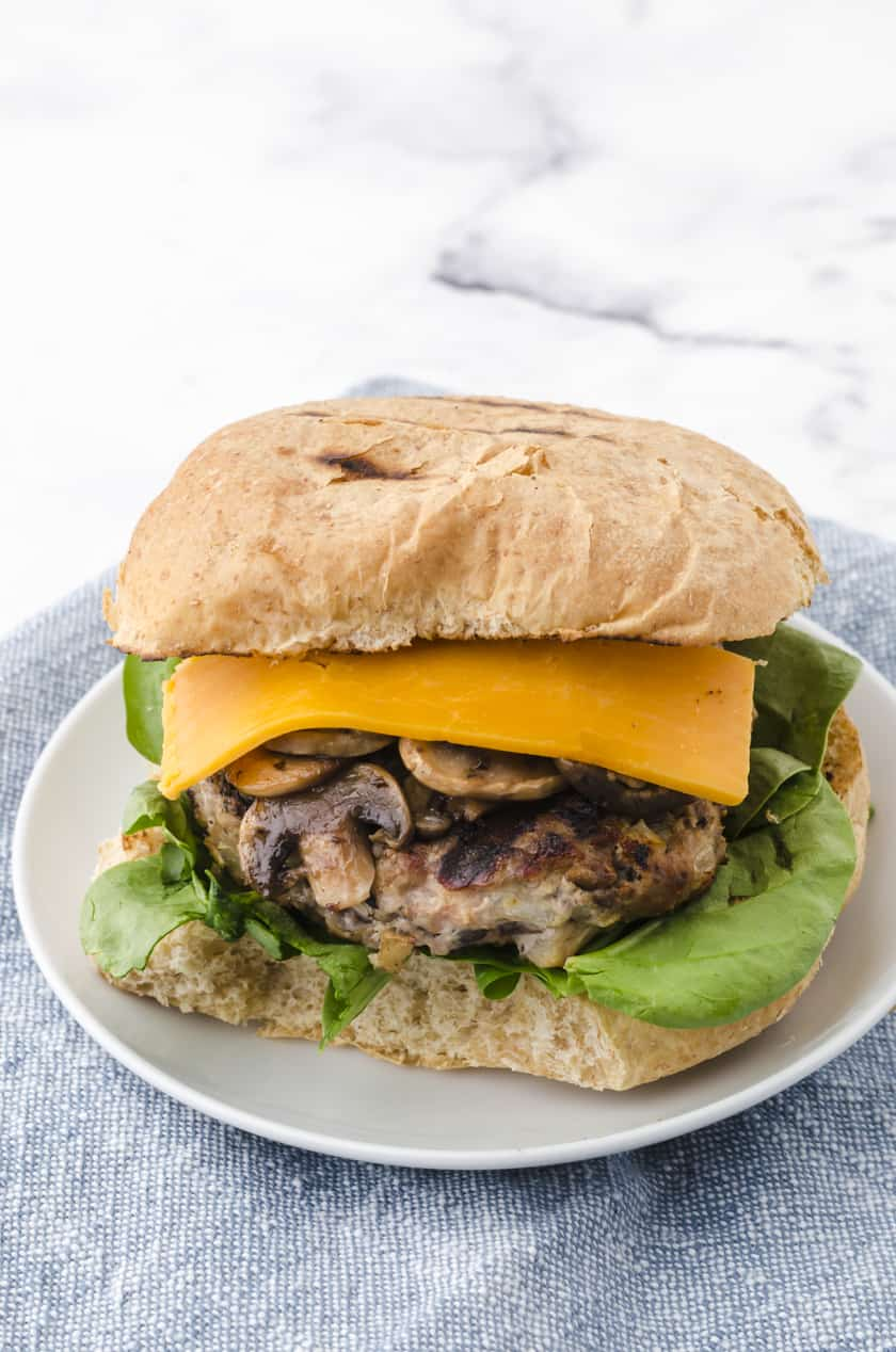 a grilled turkey burger on a plate with sauted mushrooms, lettuce, cheese and a toasted bun.