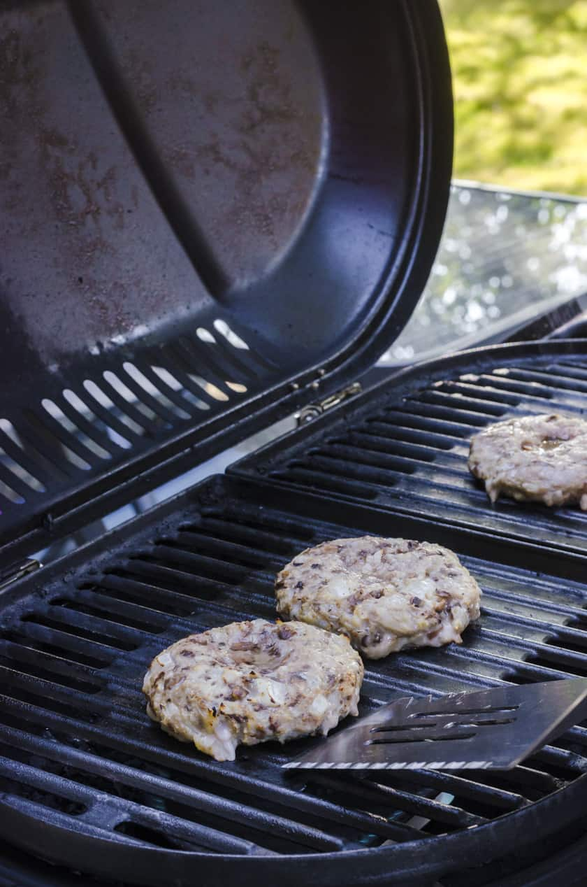 A homemade turkey burger being flipped with a large barbecue flipper.