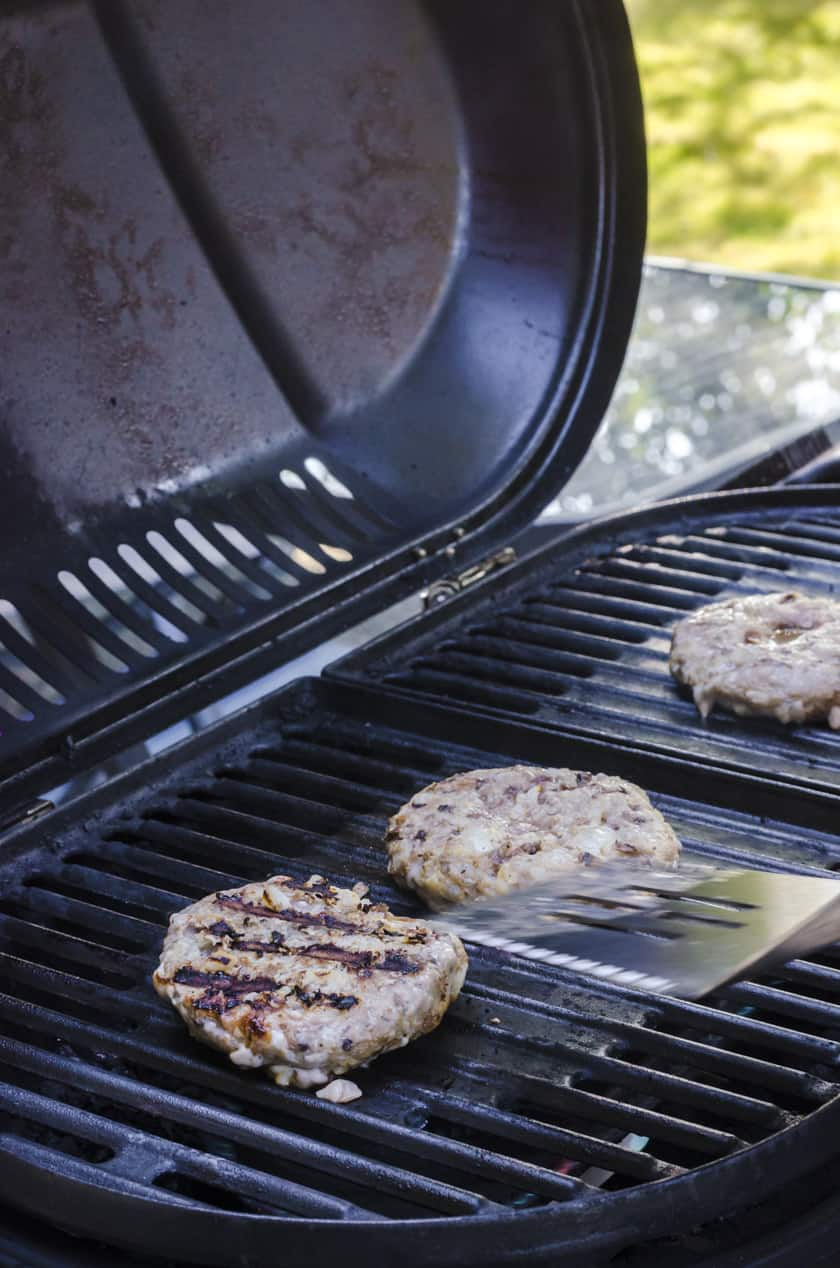A grilled turkey burger patty on a barbecue grate with the grate marks showing on the top.