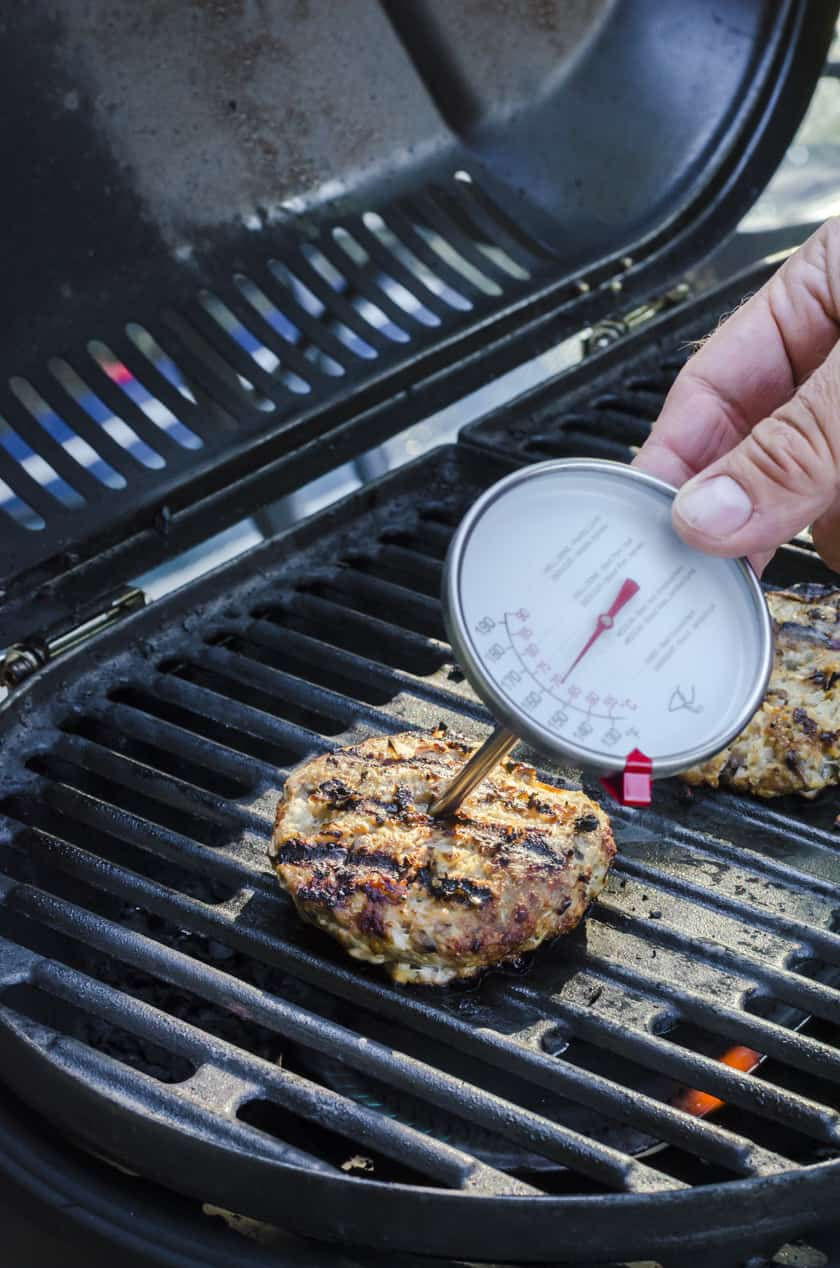 a food thermometer being places in the center of a turkey burger.