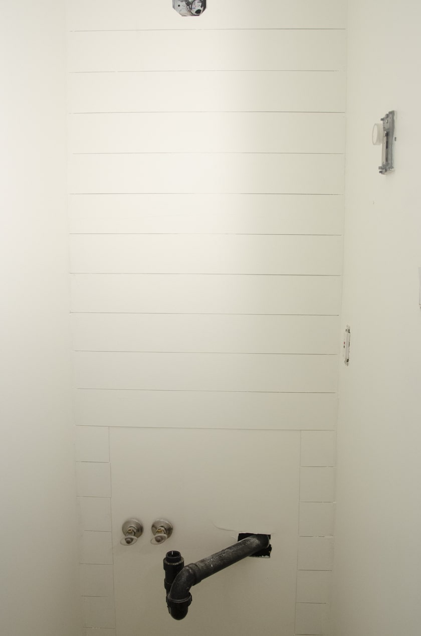 faux shiplap wall in a powdedr room where a vanity will go