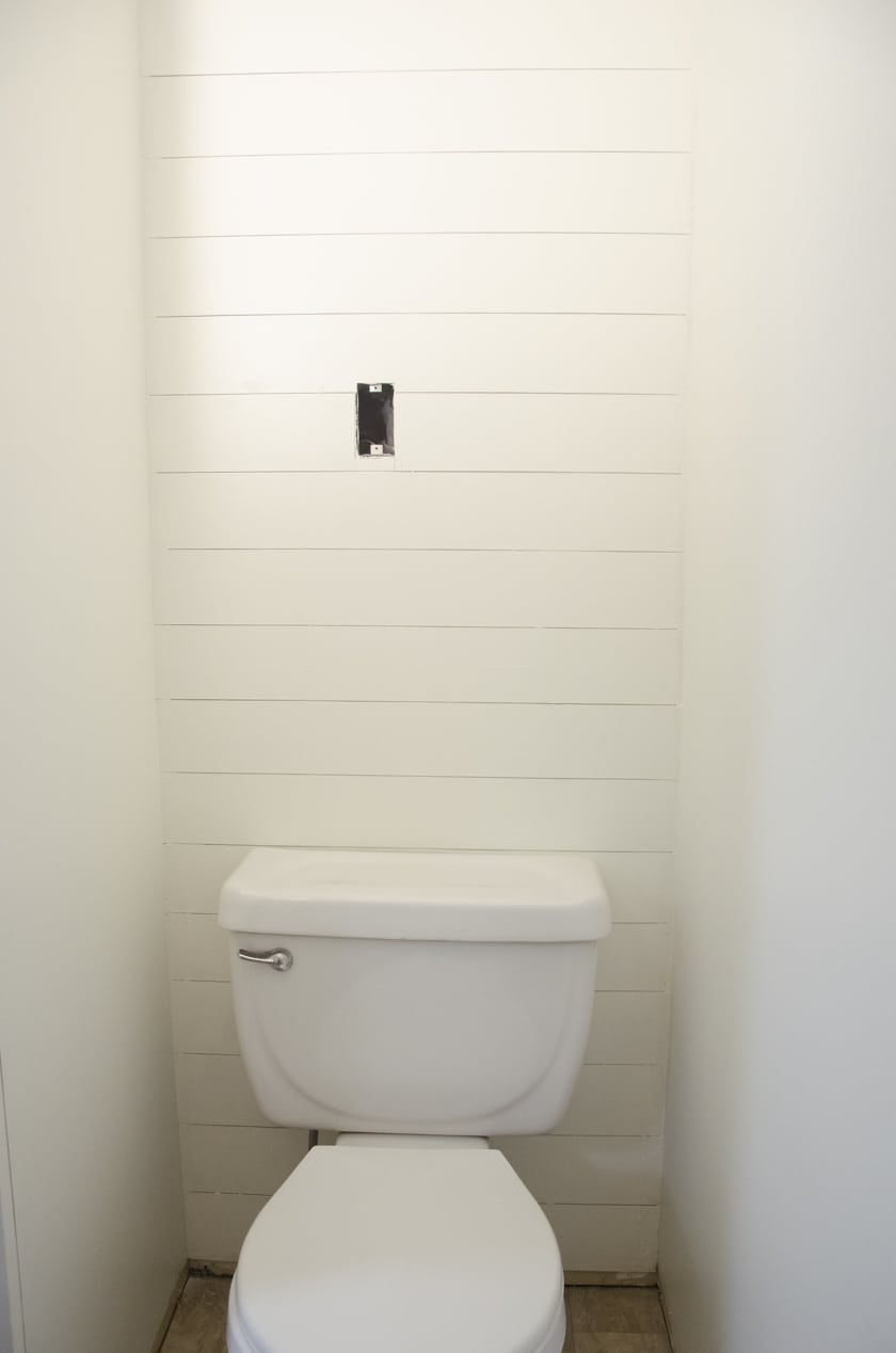 faux shiplap accent wall in a powder room behind a toilet